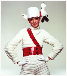 Twiggy in Snoopy Cap – Twiggy stands wearing a fur jumpsuit with a plastic Sam Browne belt and Snoopy canvas cap – 1967 Photo Bert Stern