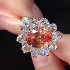 Dehres. A magnificent Oval Shape Pink-Orange Unheated Padparascha and diamond ring.