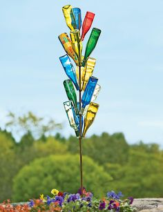 Bottle tree, I so want one in my yard.   In the Congo, it was said that colored glass attracted evil spirits and trapped them inside bottles. When the wind blew, the moaning sound made by the wind whistling in the bottles was said to be these trapped spirits.