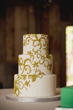 an elegant, clean lined cake with pretty green flair by http://cocopalomadesserts.com/  Photography by http://she-n-he.com