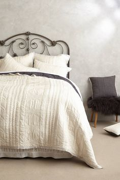 whites and grey and an iron headboard