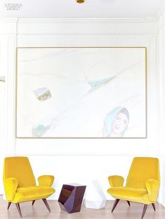Sitting area with yellow chairs and light colored artwork