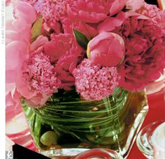 The Centerpieces Vibrantly colored centerpieces -- some low square vases with pink peonies wrapped in bear grass and garden stones, and others tall with white orchid -- alternated between tables.