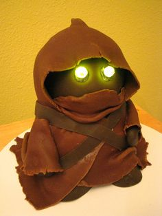 We love this awesome Jawa birthday cake. It was made by Fat Tony 1138's's wife for their friends' daughter's 5th birthday. The Jawa is made of chocolate cake and chocolate fondant and the eyes are mini party light LEDs from a craft store. We're wondering, if you have a Jawa cake but don't eat it, will it scamper off in search of other desserts to offer for sale or trade?
