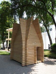 Finnish Pavilion Fue construido a partir de tramos gruesos de abeto que fueron apilados horizontalmente para crear una torre que se estrecha a hacia la parte superior, una puerta conduce al interior cuadrado, una claraboya rectangular permite la luz al día a través del los árboles.