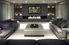 Grande living moderno con camino e tv. Stupenda illuminazione libreria e camino chiuso.