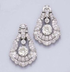 A PAIR OF ART DECO DIAMOND EAR PENDANTS Each set with an old mine-cut diamond weighing 4.37 and 5.07 carats suspended within an old mine-cut diamond geometric motif trapezoidal frame (ear clip fittings of later addition), circa 1930