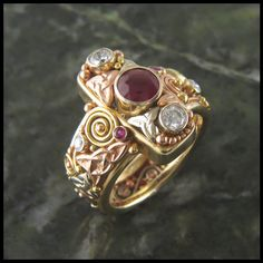 Custom Ruby and Diamond Celtic ring with 14K White, Rose, and Yellow Gold. This ring is currently available for sale in a size 7 3/4. To discuss having a ring custom made for you in this style call Wa