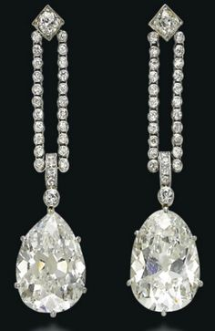A PAIR OF ART DECO DIAMOND EAR PENDANTS. Each suspending an old-cut pear-shaped diamond, weighing approximately 9.46 and 9.43 carats, from a double line of old-cut diamond collets, to a square collet surmount, 1920s, 5.0 cm, in brown leather fitted case.