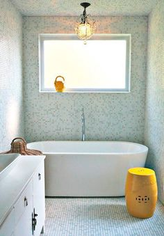 Stunning light mosaic from floor to ceiling with an organic bathtub and bright yellow details.