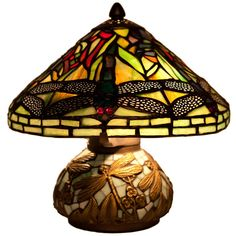 This beautiful lamp was inspired by the Hanging Head Dragonfly lamp originally designed by Louis Comfort Tiffany and Clara Driscoll. The dragonflies, in addition to the elements of green, orange, and