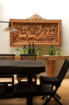 like wall art/carving and console table with green bottles