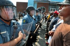 Protester Boss Bastain of St. Louis locks arms with other demonstrators as they confront Missouri State Highway Patrol troopers in front of the Ferguson police station on Monday, Aug. 11, 2014. (Robert Cohen/St. Louis Post-Dispatch)