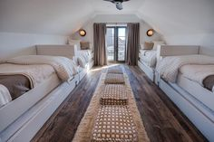Chic sleepover room features two rows of built-in twin beds dressed in white and gray bedding fitted with trundle beds facing each other across from a row of white and gray woven ottoman stools placed atop a sheepskin runner.