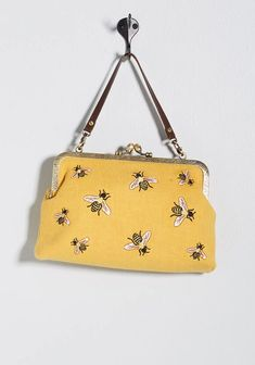 Flaunting embossed metal edges and an embroidered bee motif, this mustard yellow clutch definitely generates a buzz! Equipped with a faux-leather strap and a lengthier chain shoulder strap, this soft canvas purse is a ModCloth-exclusive way to help you ac Yellow Clutch, Yellow Purses, Luanna, Canvas Purse, Cute Purses, Unique Purses, Cute Bags, Beautiful Bags, Modcloth