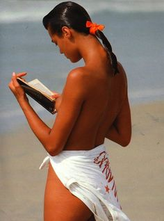 Yasmin Le Bon reading on beach in Abbronzate e anche più snelle for Moda, 19 April 1987. Photographer: Gilles Bensimon. In April 1987, Le Bon was hired by Guess? for an advertising campaign. Throughout the late 1980s, she appeared on the cover of the first American and British issues of Elle. She has also been on the covers of Vogue, V, I.D., Cosmopolitan, Marie Claire and Harper's Bazaar.