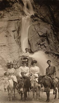 Mrs. Moritz Bernstein, her son and daughter and another woman ride on burros in front of the waterfalls at Seven Falls,Colo.  Bernstein's other son stands behind the group.  All five are wearing hats.