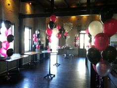 Balloon table and floor arrangements in hot pink, magenta and black