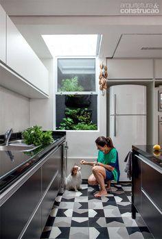 Os tons dos ladrilhos hidráulicos Bandeira pautaram os demais acabamentos na cozinha. Restaurada, a abertura no teto traz claridade suficiente para o cultivo de uma horta no poço de luz. Projeto de Consuelo Jorge.