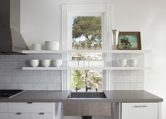 In a kitchen by Mark Reilly Architecture—winner of a Remodelista 2013 Considered Design Award—the countertops are made of honed Caesarstone in Pebble. To add heft, the architect introduced a 1 mitered edge on the front face of the counters. Kitchen Window Shelves, Warehouse Shelving, New Kitchen, Kitchen Sink, Kitchen Backsplash, Kitchen Upstairs, Floors Kitchen, Kitchen White, Backsplash Ideas