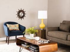 A classic mid-century living room: A beautiful brown coffee table, a brown side table, and brown tones in both the couch and the chair. To top it off, even the walls are in a brown-tone, that still looks light and friendly enough, with a fancy wall clock for extra decoration. // 13 Mid-Century Modern Living Rooms for Inspiration - Some affordable, some luxury living rooms, but all in a beautiful style with mid-century furniture