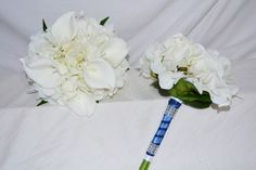Real touch and premium silk flowers  Bridal bouquet made with real touch off white hydrangea and calla lilies, featuring silk blue galaxy orchids + buds Maids bouquets consist of real touch hydrangea and calla lilies in off white  1 x Brides posy 24 cm wide 2 x maids posies 18 cm wide 2 x off white calla buttonholes 1 x off white calla, hydrangea + galaxy orchid buttonhole  ​​All wrapped with off satin with navy organza overlay & dimpled diamante collar accents
