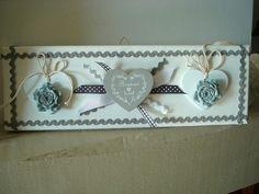 """Ce cadre déco création est réhaussé de 2 coeurs en bois blanc rehaussés de 2 roses grises le tout est agrémenté d'un coeur """"Bonheur"""" gris et de plusieurs rubans de couleur blancs et gris.  C'est une création Déco à Coeur, et une pièce unique.  Dimension : 30 x 10 cm"""