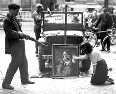 Members of the French Resistance express their contempt by posing in front of a defaced portrait of Adolf Hitler in Paris the day after the German garrison surrendered in the city. Paris, Île-de-France, France. 26 August 1944.