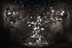Chiharu Shiota's black yarn installation with a desk and loose papers.