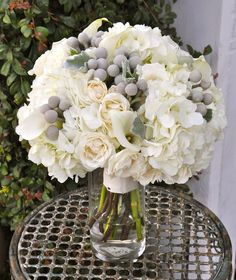 White hydrangea, spray roses, mini calla lilies, dusty miller and silvery brunia berries.