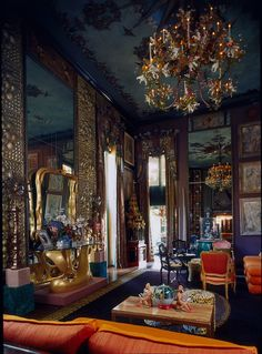 Dark purple walls with heavy draperies. Orange upholstery. Eclectic mix of accessories and art.