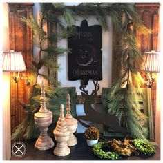 Faux greenery garland completes this Christmas winter foyer vignette! Paired with wood architectural wall light sconces, trio of wood turned finials, boxwoods, rusty deer, chippy shutters and the black Merry Christmas sign balances out the look to work with the black dresser. Wall Sconce Lighting, Sconces, Black Dressers, Merry Christmas Sign, Greenery Garland, American Decor, Shutters, Vignettes, Foyer