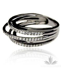 Ciekawa obrączka wykonana ze srebra próby 925, oksydowana dla nadania ciemnej barwy. W wyrobie osadzono kontrastujące, białe Cyrkonie. Pierścionek składa się z kilku drobnych obrączek o różnym kącie i rozmiarze, połączonych w jedno. Rozmiar pierscionka to 13, szerokość samej obrączki to około 0,8 cm.