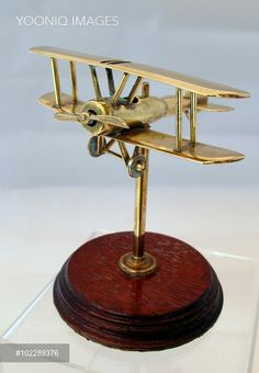 First World War bi-plane with a bullet fuselage on a wooden base with a brass post. Trench Art