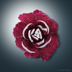 Pivoine Mystérieuse detachable clip, Palais de la chance™ collectionWhite gold, round diamonds, red gold, Mystery Set™ rubies.The flower in Mystery Set™ rubies and diamonds of the Pivoine Mystérieuse necklace - detachable in order to become a clip - stands out against the sparkling foliage, its diamond hemmed petals seeming to blossom before our eyes. With its voluptuous corolla ranging from flaming red to powder white, the pivoine has dazzled the Maison since the 1930s.