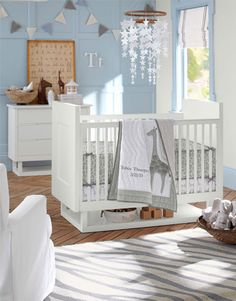 Bright white furniture pairs with soft gray and blue hues add to the room's light, breezy feel