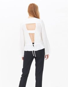 Sandro top with slightly flared long sleeves and a round neckline. Pleasant, flowing fabric. Large fancy openings at the back, fastened with a tie that accentuates the waist. Small bow on the shoulder. Very chic, you can wear this top day or night. Model is wearing a size 1.
