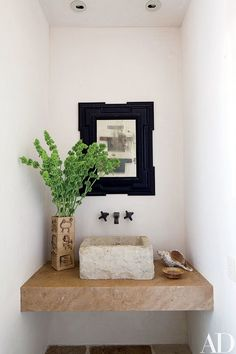 An antique Flemish mirror graces the powder room  baño de visitas pequeño lavabo espejo