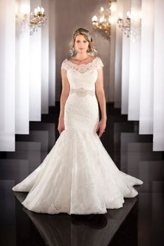 463 Fit-and-flare designer bridal gown has an elongated bodice and a full skirt with multiple layers of European laces giving a textural effect. Comes with a detachable lace illusion neckline. Beaded sash available separately.