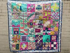 A traditional handmade patchwork quilt made with modern fabrics.  Measures approximately 38 x38 or 95cm x 95cm  A machine sewn double binding and a lot of hand quilting make this a lovely blanket that will brighten up any lounge, bedroom or nursery and continue to look great for