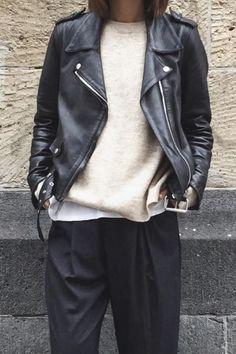 Zwarte wortelbroek met wit t-shirt, lichte wollen trui en leren jasje.
