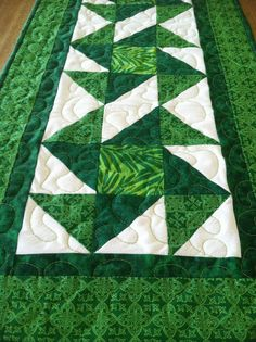 This table runner is made just in time for St. Patricks Day and has a different style of pinwheel block. Each block is constructed with three green