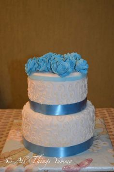 Wedding Cakes - 2 Tier White and Blue Fondant Worked Cake with Blue Fondant Buttercream Rosettes | All Things Yummy #twotier #engagement #cake for a #blueandwhite #theme..