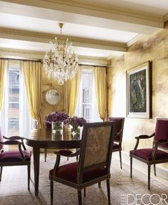 Detailed rooms pay homage to the trees and sky outside | Gold walls | Gold Distressed Walls | Gold Drapes | Elegant Traditional Crystal Chandelier | Ceiling with Dressed Beams | Elegant Oval Mahogany Table | Merlot Red Velvet Dining Chairs with Detailed backs | Elegant Dining Room | Traditional Dining Room