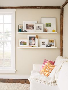 I like this type of picture display. Really charming room.of course the huge window, the natural woodwork and the scirbbly pink and orange pillows give this room it's personality Photo Shelf, Picture Shelves, Photo Wall, Picture Ledge, Picture Walls, Picture Frames, My Living Room, Home And Living, Living Room Decor