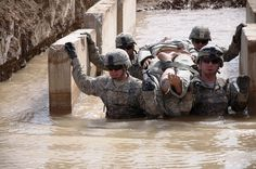 Soldiers with the 2nd Advise and Assist Brigade, 1st Infantry Division, United States Division – Center navigate through a water obstacle during the litter-carry obstacle course during the brigade's Best Medic Competition June 19, 2011 at Camp Liberty, Iraq. Teams representing battalions from around the brigade participated in the competition, designed to mimic the Army's Expert Field Medical Badge course.