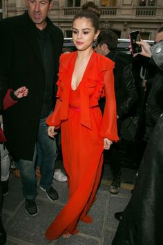70 of Selena Gomez's style moments: Selena is seen wearing a red silk ruffled gown and high bun