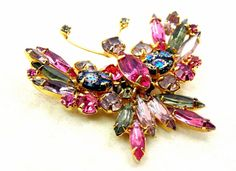 This vintage pink crystal glass rhinestone butterfly brooch/pin has black iridescent cabochons. Made in the 1960s, she has lovely pink, light lavender and gray rhinestone navettes. All of the rhinestones are prong set. There is a little wear to the gold tone metal near the antennae. The