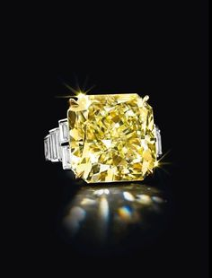 A colored diamond ring. Set with a cut-cornered modified square-cut fancy yellow diamond, weighing approximately 26.18 carats, flanked on either side by four baguette-cut diamonds, mounted in gold and platinum. With report 1142960186 dated 22 August 2012 from the Gemological Institute of America stating that the diamond is fancy yellow, natural color, internally flawless clarity.