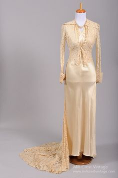 Designed in the 40's this absolutely stunning vintage wedding gown is done in a champagne toned liquid silk satin with an accompanying asymmetrical sheer lac...